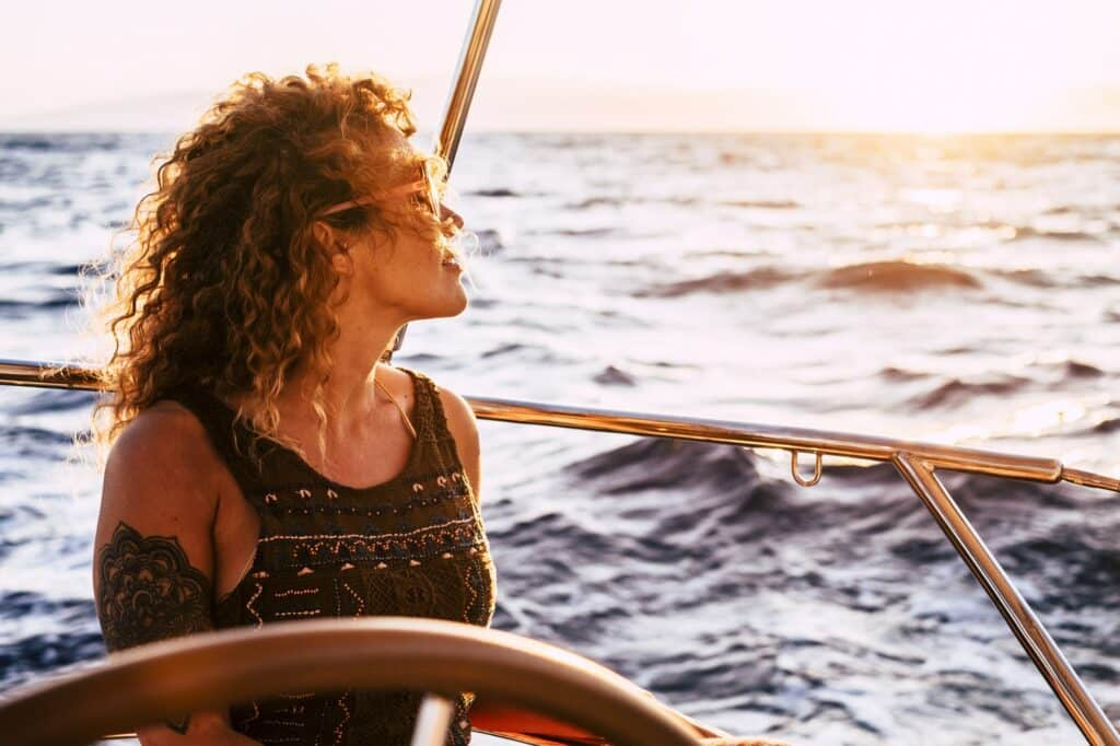 femme heureuse et épanouie sur un bateau