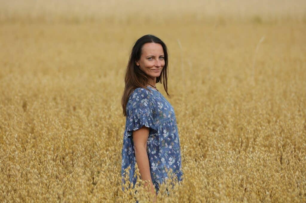 femme heureuse dans un champ regarde la caméra