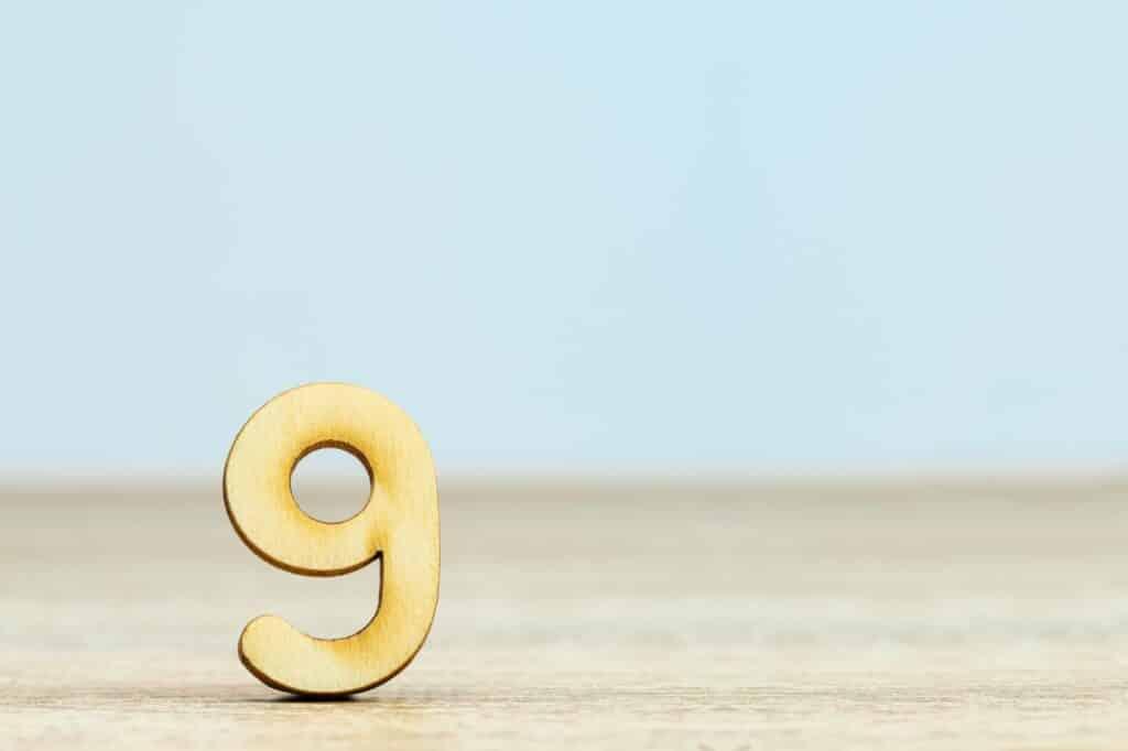nombre 9 en bois posé sur une table