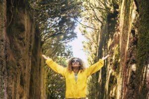 Femme heureuse lève les bras dans la nature